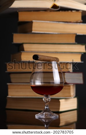 Glass of brandy on a reflective surface with books and cigar