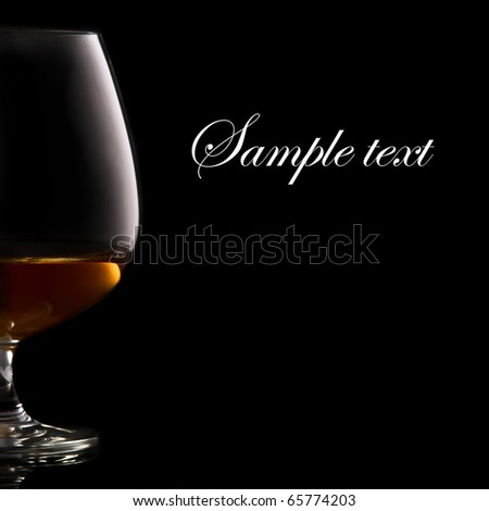 Glass of brandy over black background and space for your own text on right - stock photo