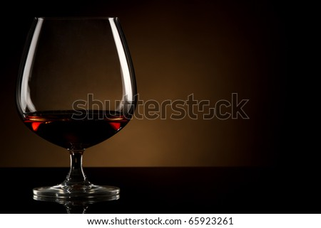 Glass of brandy over brown background - stock photo