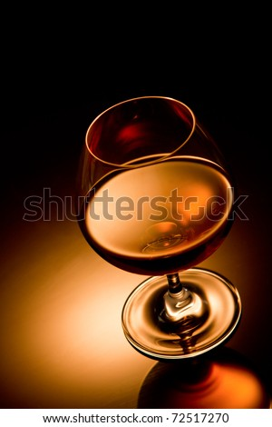Glass of brandy over gold gradient background - stock photo