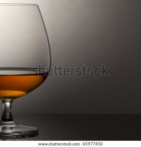 Glass of brandy over grey background - stock photo