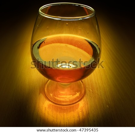 Glass of brandy with light on dark - stock photo