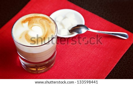 Glass of capuccino with sugar on red background - stock photo