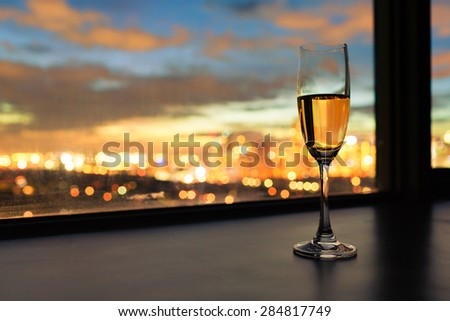 Glass of champagne and a beautiful city view.  - stock photo