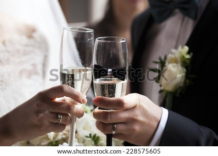 Glass of champagne in a hand of the groom and bride  - stock photo