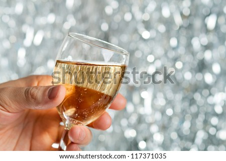 Glass of champagne in man's hand against silver background - stock photo