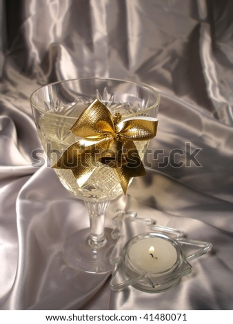 Glass of champagne with a gold bluebell on it and candlestick in form fir next to him - stock photo