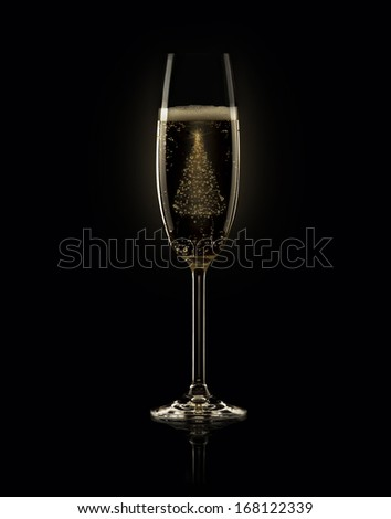 Glass of champagne with Christmas tree on black background - stock photo