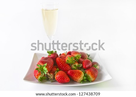 Glass of champagne with plate full of strawberries behind isolated on a white background - stock photo