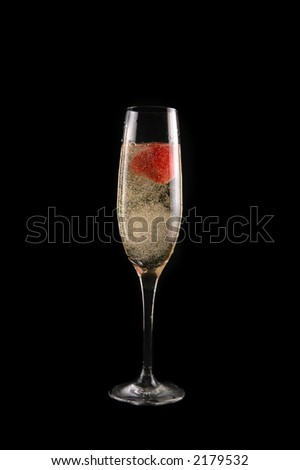 glass of champagne with strawberry on black background - stock photo
