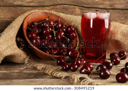 Glass of cherry juice on wooden background - stock photo