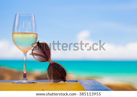 glass of chilled white wine and sunglasses on table near the beach