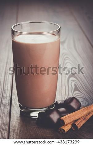 glass of chocolate milkshake and cinnamon on the table - stock photo