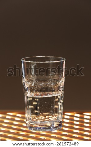 Glass of clean mineral water on lattice surface and dark color background - stock photo