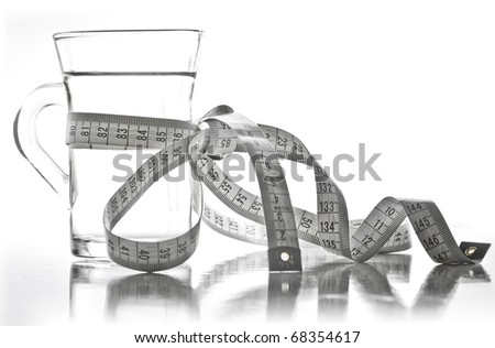 Glass of clean water with a measuring tape. Reflected in the table. - stock photo