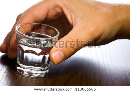 glass of clear alcohol in hand - stock photo