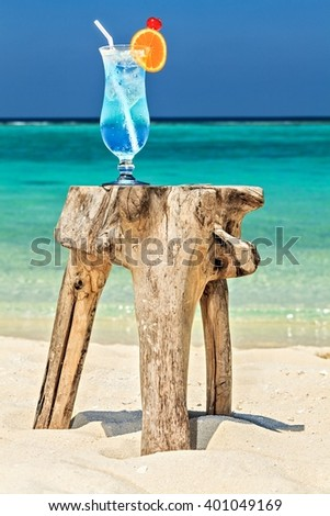 Glass of cocktail is on original  beach table is made from trunk of tree - stock photo