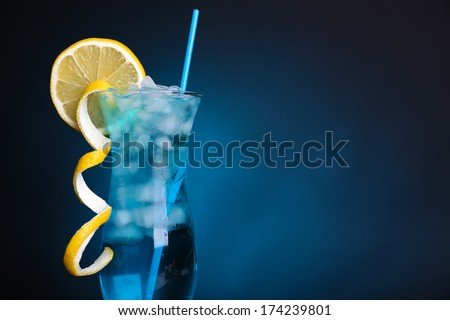Glass of cocktail on table on dark blue background - stock photo