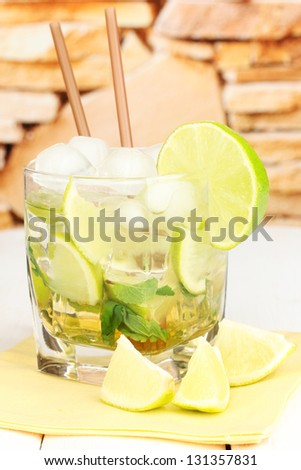 Glass of cocktail with lime and mint on white wooden table on stone wall background - stock photo