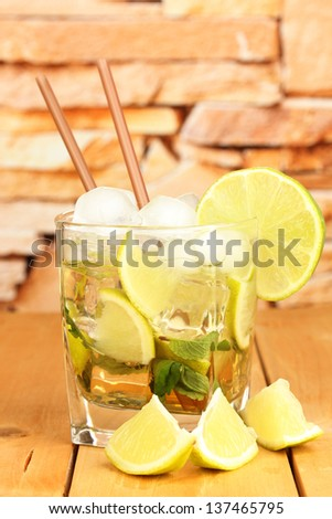 Glass of cocktail with lime and mint on wooden table on bright background - stock photo