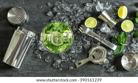 Glass of cocktail with lime, mint, ice. Drink making bar tools, shaker, ingredients - stock photo