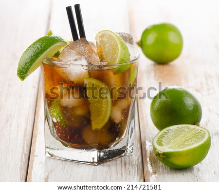Glass of cocktail with rum, lime and ice. Selective focus - stock photo