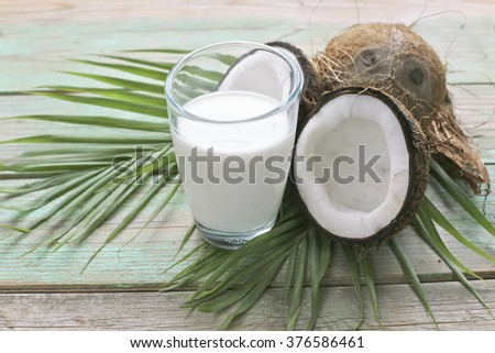 Glass of coconut milk with coconut and palm leaves  - stock photo