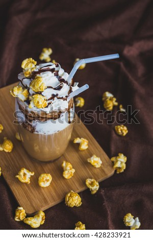 Glass of coffee latte with whipped sour cream, caramel popcorn  and chocolate - stock photo