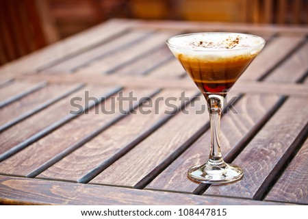 Glass of coffee with different layers served on restaurant table