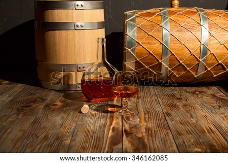 Glass of cognac and a bottle of some old oak barrel