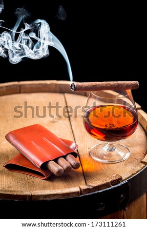 Glass of cognac and cigar on old barrel - stock photo