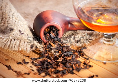 Glass of cognac and pipe with tobacco on wooden table with linen canvas - stock photo