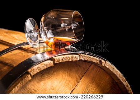 Glass of cognac on the old wooden barrel - stock photo