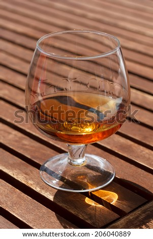 Glass of cognac standing on a wooden table in sunlight. - stock photo