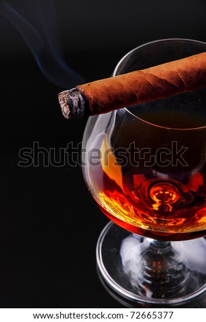 Glass of cognac with a cigar - stock photo