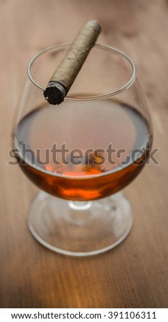 Glass of cognac with a cigar. Selective Focus