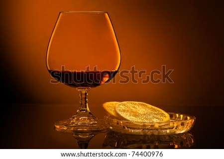 Glass of cognac with lemon on brown background - stock photo