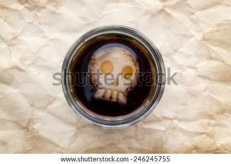 Glass of cola drink with skull shape ice top close up view, soft focus - stock photo