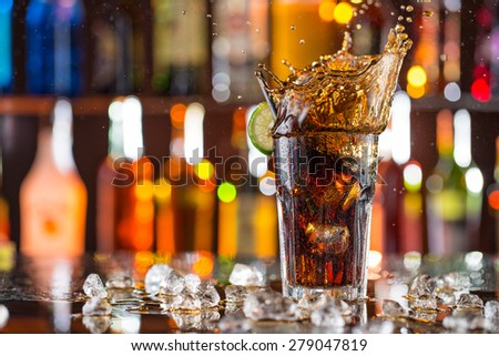 Glass of cola on bar desk with splashing liquid, close-up. - stock photo