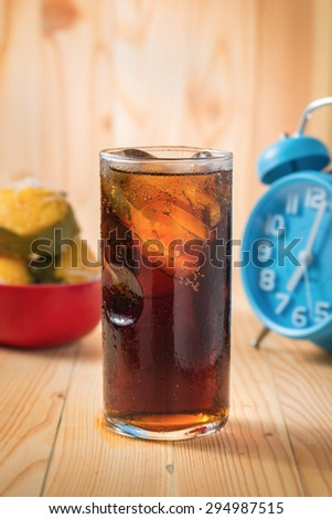 glass of cola with ice cubes and bule clock on wood background - stock photo