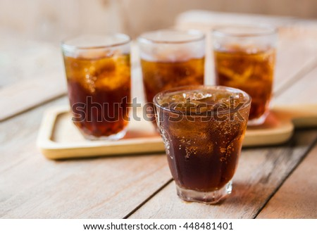 glass of cola with ice cubes on table.