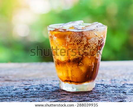 glass of cola with ice cubes on wood table. - stock photo