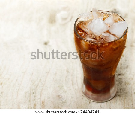 Glass of cola with ice on wooden plank - stock photo