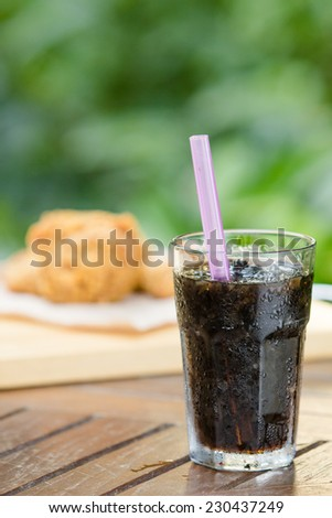 glass of cola with ice on wooden table - stock photo