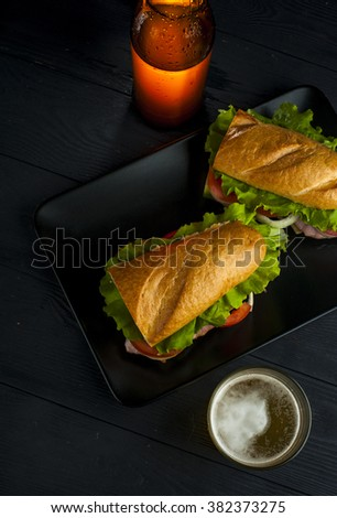Glass of cold beer, black plate with sandwiches and beer bottle on wooden table. Fast food. - stock photo