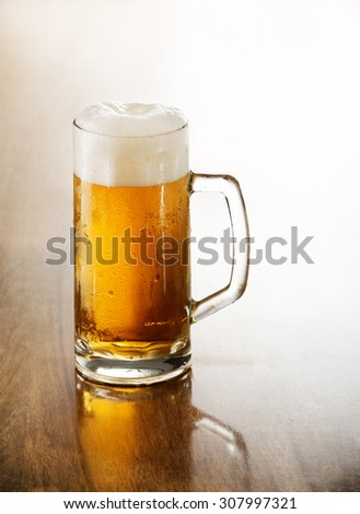 Glass of cold beer on a wooden table.