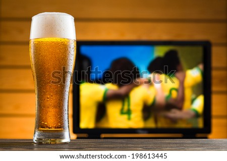 Glass of cold beer on the table, football match in background - stock photo