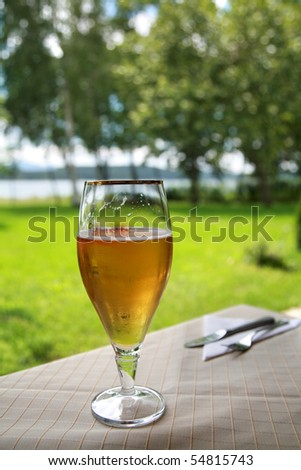 Glass of cold beer on white tablecloth and cutlery