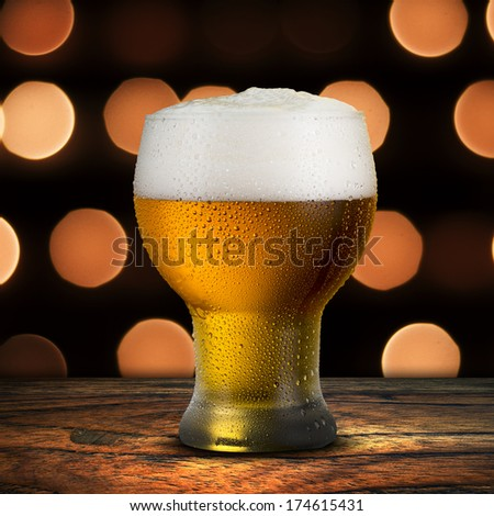 Glass of Cold Beer on wood table with light bokeh background