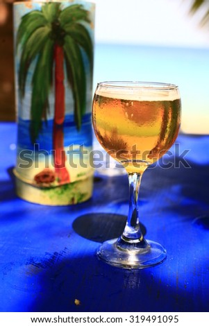 glass of cold beer with foam on the table. Against the background of the sea